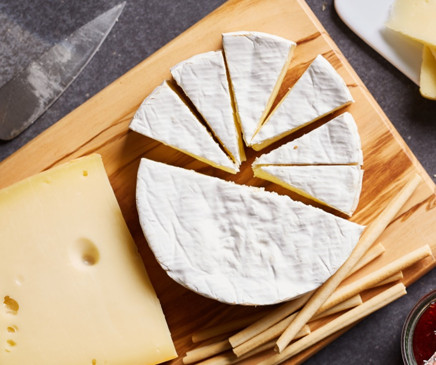 Block of cheese and cheese wheel on cutting board